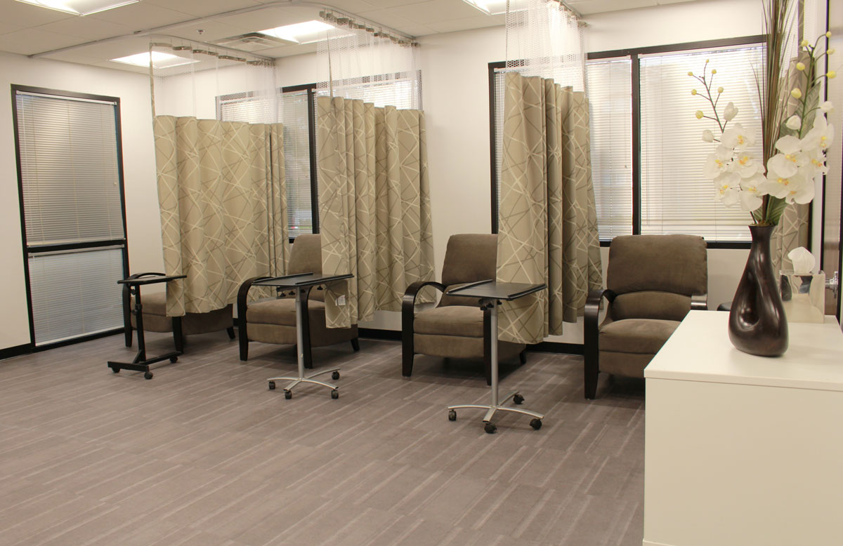 room with multiple curtained sections with chairs
