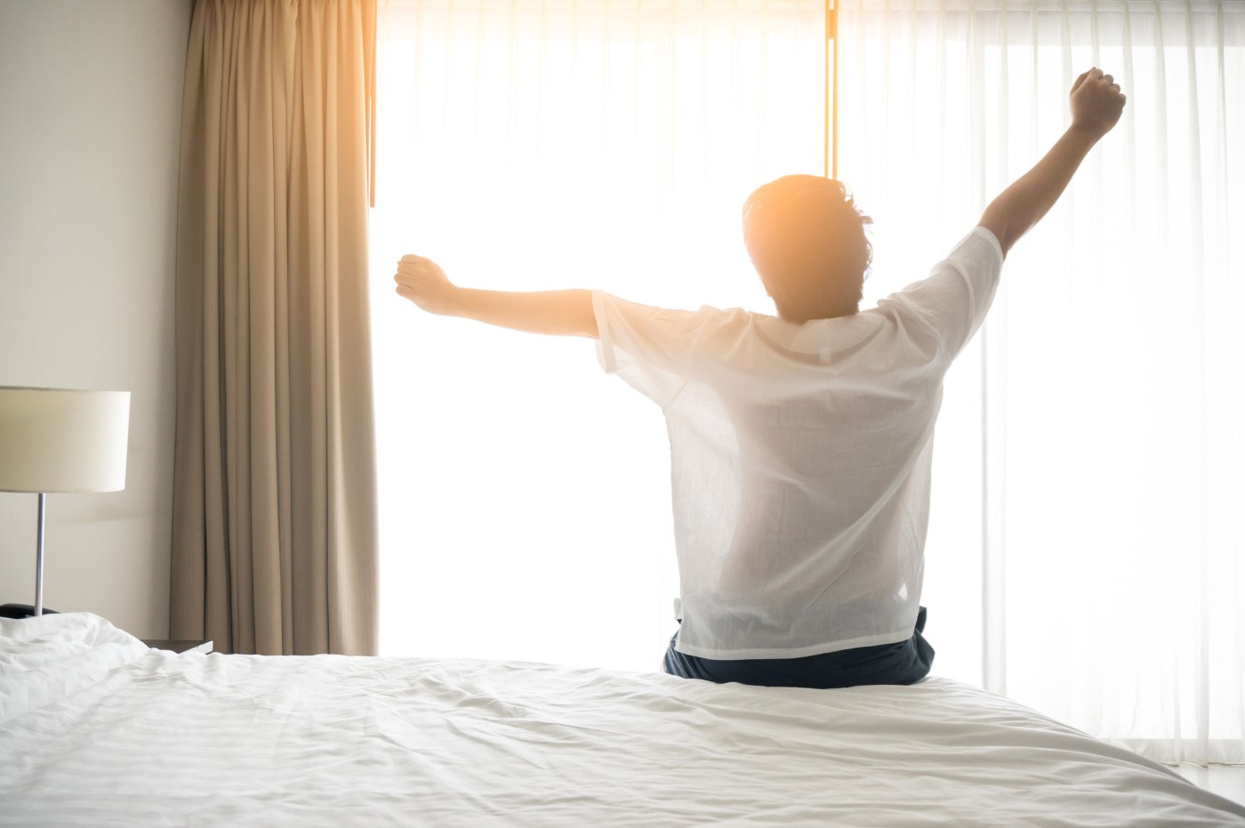 Importance of Sleep in Pain Control | Man wake up and stretching in morning with sunlight